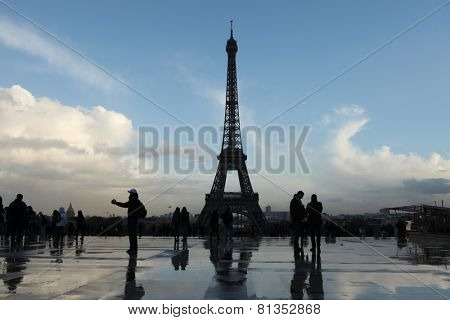 PARIS, FRANCE - NOVEMBER 14, 2013: People walk in front of the Eiffel Tower on the Champ de Mars in Paris, France.