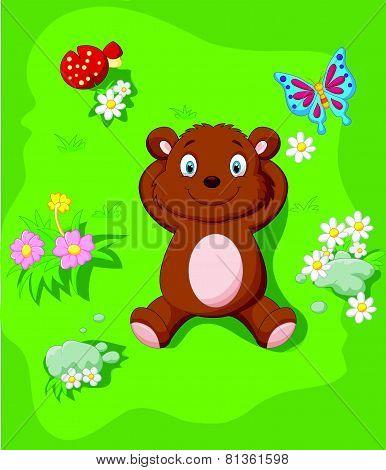Happy bear cartoon lying down on the grass