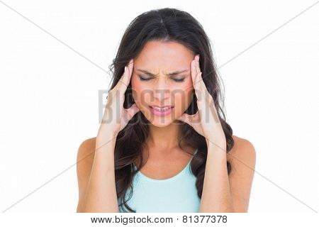 Pretty brunette getting a headache on white background
