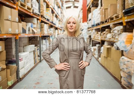 Unsmiling manager placing her hands on her hips in a large warehouse