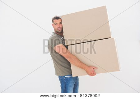 Man carrying cardboard moving boxes at home in the living room