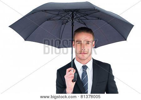 Unsmiling businessman sheltering under umbrella on white background
