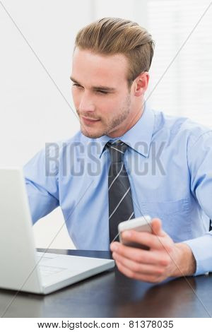 Smiling businessman holding mobile phone in his office