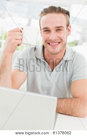 Smiling businessman holding cup and using laptop in his office