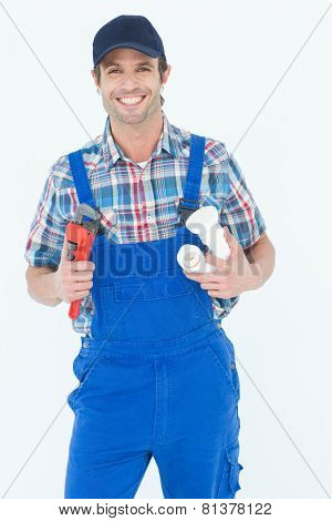 Portrait of confident plumber holding monkey wrench and sink pipe over white background