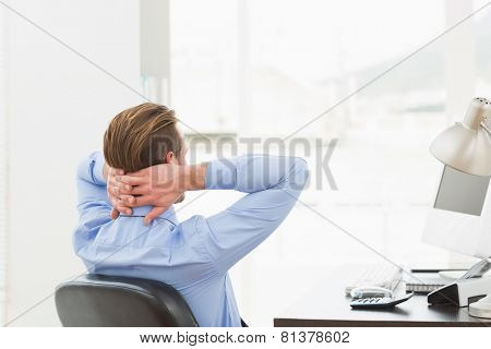 Businessman relaxing in a swivel chair leaning back in his office
