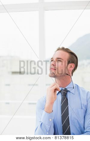 Businessman holding glasses in day dreaming in his office