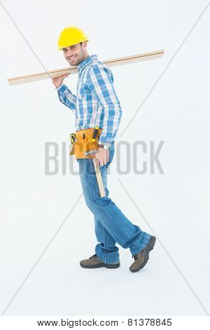 Full length side view of smiling worker carrying wooden planks over white background