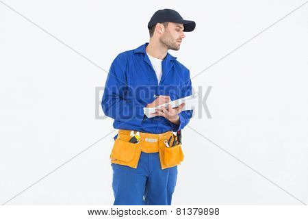 Repairman looking away while writing on clipboard against white background