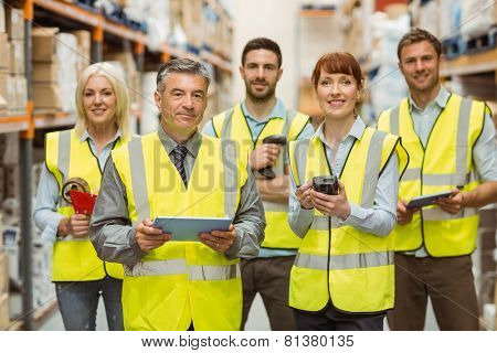 Smiling warehouse team looking at camera in a large warehouse