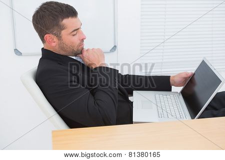 Relaxed businessman with a laptop in his office