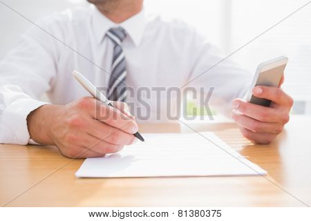Businessman writing on a paper in his office
