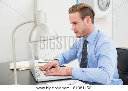 Serious businessman using his laptop in his office