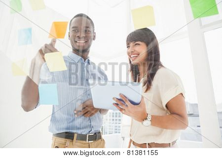 Smiling teamwork reading sticky notes and using tablet in the office