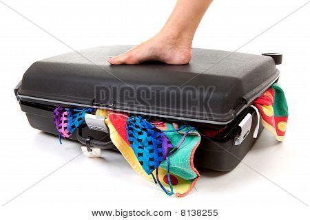 Foot On Stuffed Suitcase