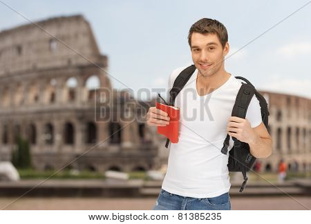 people, travel, tourism and education concept - happy young man with backpack and book travelling over coliseum background