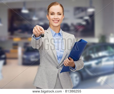 auto business, car sale, gesture and people concept - happy businesswoman or saleswoman with folder giving car key over auto show background