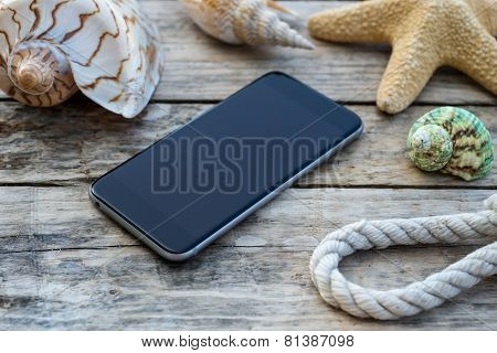 Wooden background with starfish, phone and shell - maritime decoration.