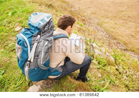 adventure, travel, tourism, hike and people concept - man with backpack sitting on ground from back