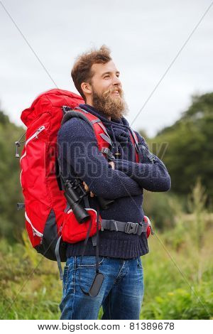 adventure, travel, tourism, hike and people concept - smiling man with red backpack and binocular outdoors