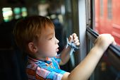 picture of passenger train  - Curious little boy with toy plane looking out of open train window  - JPG