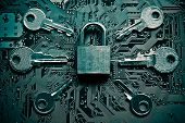 stock photo of cybercrime  - a security lock on a computer circuit board surrounded by keys - JPG