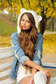 stock photo of debonair  - Portrait of young smiling woman dressed in cute hat with ears - JPG