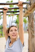 stock photo of swing  - Woman training on fitness brachiation ladder or monkey bars hanging swinging from rung to rung as part of crossfit workout routine - JPG