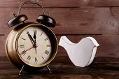 image of analog clock  - Retro clock with decorative bird on table on wooden background - JPG