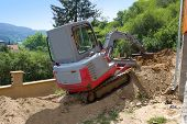 picture of excavator  - a small excavator provides garden at the house - JPG