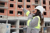 stock photo of inspection  - Construction site manager at construction site is inspecting ongoing production and commanding work by use of a radio.