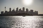 foto of cbd  - Sydney distant CBD silhouette of skyscrapers and towers at sunset against the sun summer time heat in the city - JPG