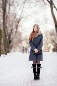 pic of stroll  - Winter full length portrait of a cute redhead lady in grey coat and scarf strolling in the park - JPG