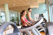 stock photo of cardio  - Couple in fitness center working out on cardio machine - JPG