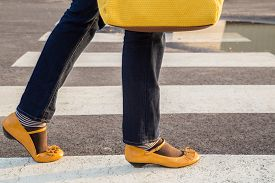 stock photo of mary jane  - Woman passing crosswalk with yellow purse and yellow shoes - JPG