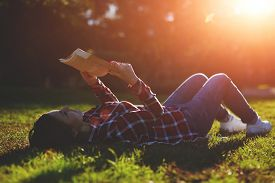picture of grass area  - A young woman lying on the grass and reading a book lovely young girl reading a book while lying in a field of grass - JPG