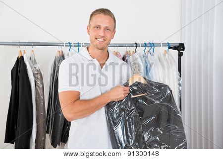Man Holding Coat In Dry Cleaning Store
