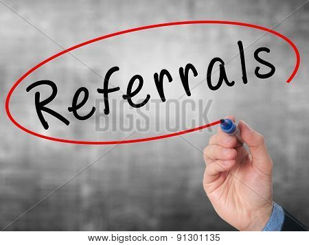 Man Hand writing Referrals with marker on virtual screen.