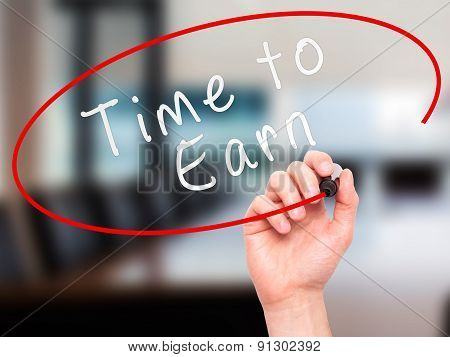 Man Hand writing Time to Earn with marker on transparent wipe board.