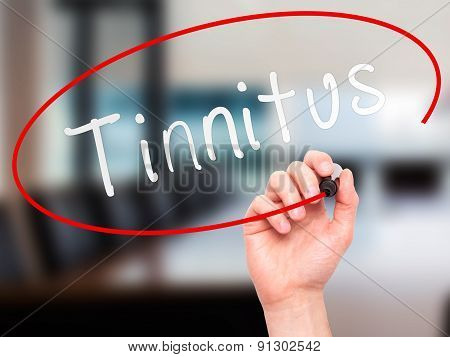 Man Hand writing Tinnitus with marker on transparent wipe board.