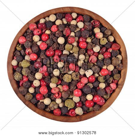 Colored Pepper In A Wooden Bowl On A White