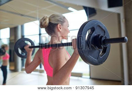 fitness, sport, training, people and lifestyle concept - happy woman flexing muscles with barbell in gym
