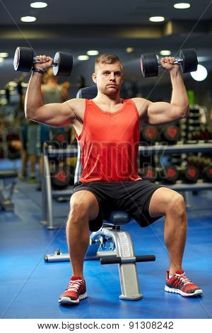 sport, fitness, bodybuilding, lifestyle and people concept - young man with dumbbells flexing muscles in gym