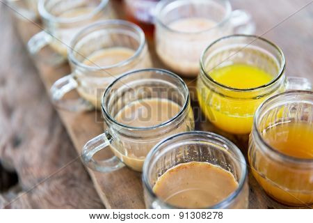 drinks and sale concept - glasses of juice at market stall or restaurant