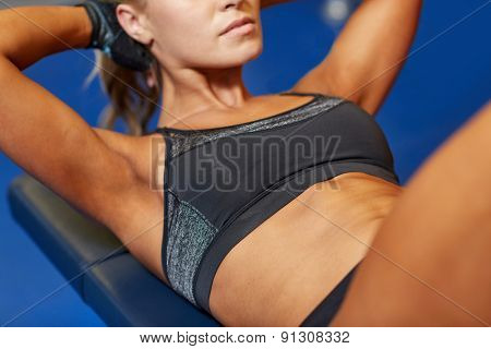 fitness, sport, training and lifestyle concept - close up of woman flexing abdominal muscles on bench in gym