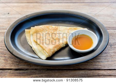 food, morning and eating concept - close up of plate with pancakes and honey or jam on table