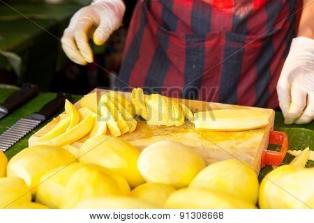 cooking, asian kitchen, sale and food concept - close up of cook hands and mango on cutting board at street market