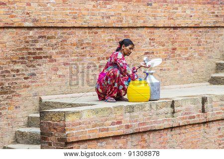 Nepali Woman Fills Up The Water Bottle