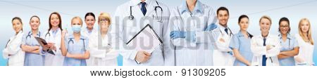 medicine, people, cardiology and health care concept - close up of nurse and male doctor holding cardiogram with medical team over blue background