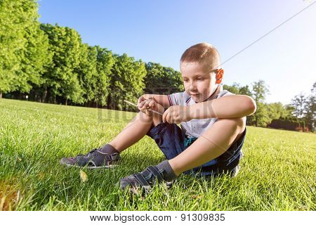 happy little boy playing on the grass